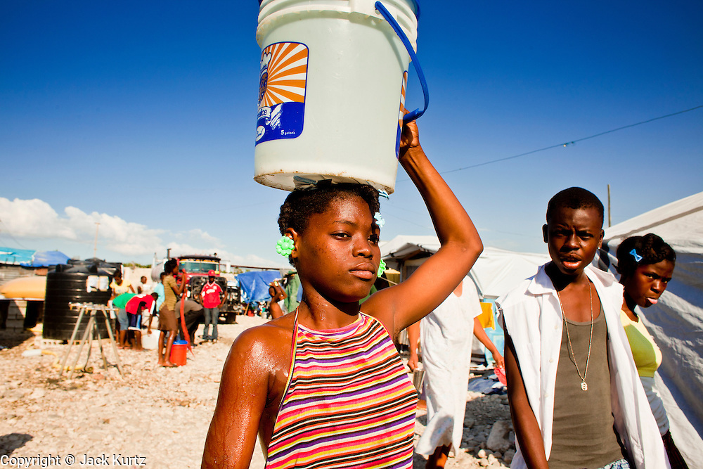 18 NOVEMBER 2010 - PORT-AU-PRINCE, HAITI:  A woman carries a bucket of untreated water home in Cite Soliel in Port-au-Prince. Cite Soleil, a sprawling slum area in PAP is ground zero for the cholera epidemic in the Haitian capital. An outbreak of cholera in northern Haiti about a month ago has spread across the nation. Tens of thousands of people have been hospitalized and treated for cholera and more than 1,100 have died. Cholera is a water borne illness that causes severe diarrhea and death by dehydration in a matter of hours.      PHOTO BY JACK KURTZ  choleraepidemic