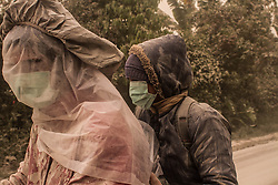 August 2, 2017 - Karo, Sumatra, Indonesia - Villagers wearing masks while volcanic ash spews from Mount Sinabung as seen from Beganding Village at Karo, North Sumatra, Indonesia. Mount Sinabung is one of the most active volcanos in Indonesia. (Credit Image: © Ivan Damanik via ZUMA Wire)