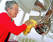 Peggy Braithwaite (now deceased) cleaning the lamp at Walney lighthouse near Barrow-in-Furness, Cumbria, UK. This lighthouse offers protection from the dangerous sandbanks of this area of Morecambe Bay. The lighthouse is owned by the Port of Lancaster Commissioners and was run for many years by Britain's only female lighthouse keeper, Peggy Braithwaite. In 2003 it was updated to an unmanned station.