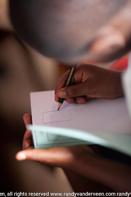 kibuye and nyrasunge Rwanda.Photo Randy Vanderveen.Rwanda.A Rwandan boy writing in a notebook.
