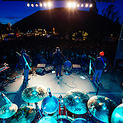 Robert Earl Keen performs to a packed crowd in Jackson, Wyoming. Photograph from behind drummer Tom Van Schaik looking out to the crowd - stage light colors.