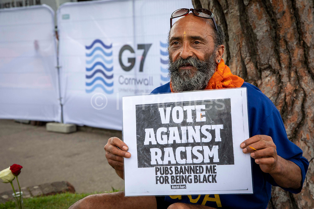 A peaceful one man meditation protest about racism by activist Alfonso Buller outside the G7 media centre on the 11th of June 2021 in Falmouth in Cornwall, United Kingdom. Over 5000 police officers from forces across the UK are in Cornwall this weekend for the G7 world leaders summit, Alfonso spent time meditation outside the media centre to bring peace to everyone attending.