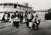 Imigrants to US landing at Ellis Island circa 1900. They head for the processing centre carrying paper with entry number which they hope will soon be traded for a visa. Photograph.