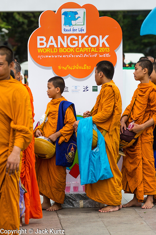 """23 APRIL 2013 - BANGKOK, THAILAND:  Buddhist monks and novices walk past a sign announcing Bangkok is the 2013 UNESCO World Book Capital. UNESCO awarded Bangkok the title. Bangkok is the 13th city to assume the title of """"World Book Capital"""", taking over from Yerevan, Armenia. Bangkok Governor Suhumbhand Paribatra announced plans that the Bangkok Metropolitan Administration (BMA) intends to encourage reading among Thais. The BMA runs 37 public libraries in the city and has modernised 14 of them. It plans to build 10 more public libraries every year. Port Harcourt, Nigeria will be the next World Book Capital in 2014. .PHOTO BY JACK KURTZ"""