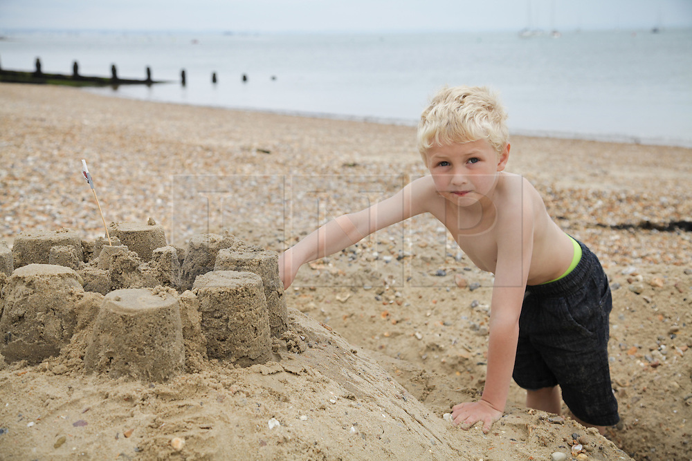 © Rob Arnold.  24/05/2015. Isle of Wight, UK. Luis (aged 6) building a sand castle and enjoying the Bank Holiday Sunday weather at The Duver beach in St. Helens on the Isle of Wight today, Sunday 24th May 2015. Today started warm with sunny spells, and clouded over later in the day in the South of England. Photo credit : Rob Arnold
