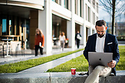 Businessman working on a laptop sat on a wall outside the cafes and corporate offices in the banking and finacne are of St Helier, Jersey, CI