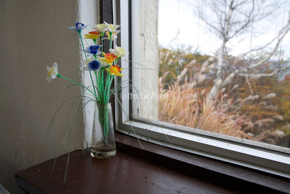 artificial flowers in windowsill