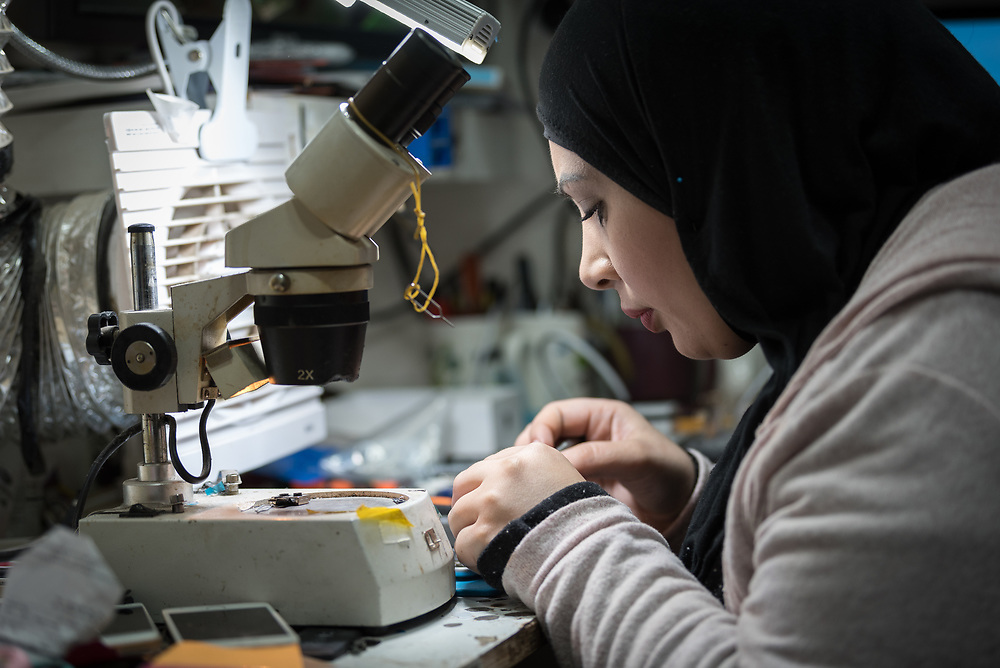 27 February 2020, Ramallah, Palestine: 29-year-old Jihad Albaba, from the Am'ari Camp, works in a small shop in Ramallah, after graduating from studies in Telecommunication at the Lutheran World Federation vocational training centre in Ramallah. Here, she works on fixing the wifi functionality of a mobile phone.