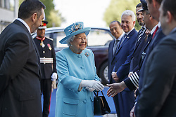 Queen Elizabeth II is accompanied by Chief Executive of British Airways, Alex Cruz (left) as she greets company executives during her visit to the headquarters of British Airways at Heathrow Airport, London, to mark their centenary year.