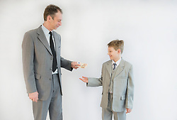 Father handing money to his son, smiling
