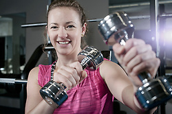 Young woman doing exercise with dumbbells in the gym, Bavaria, Germany