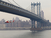 U.S. coast guard helicopter flying under the Manhattan Bridge New York City.