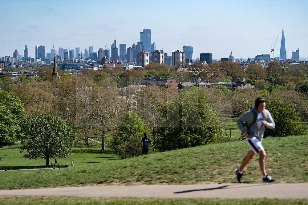© Licensed to London News Pictures. 14/04/2020. London, UK. A clear view of the London city skyline, all the way through to Canary Wharf, from Primrose Hill in North London, during a pandemic outbreak of the Coronavirus COVID-19 disease. Air quality and pollution levels in the capital have been significantly lower since the introduction of a lockdown to fight the spread of COVID-19 . Photo credit: Ben Cawthra/LNP