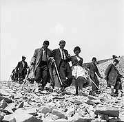 Between 50.000 and 60.000 pilgrims, young and old, from all parts of Ireland and abroad, climbed the rugged slopes of Croagh Patrick to take part in the annual pilgrimage.  Some of the pilgrims made their way over stoney ground.<br /> <br /> 29th July 1962