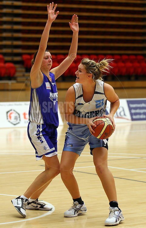 PERTH, AUSTRALIA - JULY 16: Emma Lobb of the Tigers looks to drive past Rosie Tobin of the Hawks during the week 18 SBL game between the Perry Lakes Hawks and the Willetton TIgers at The State Basketball Center on July 16, 2011 in Perth, Australia.  (Photo by Paul Kane/All Sports Photography)