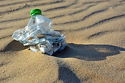 Pllastic bottle pollution on a sandy beach.