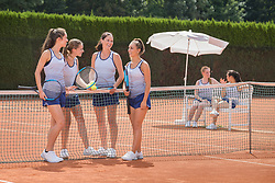 Group of women playing tennis on a sunny day, Bavaria, Germany