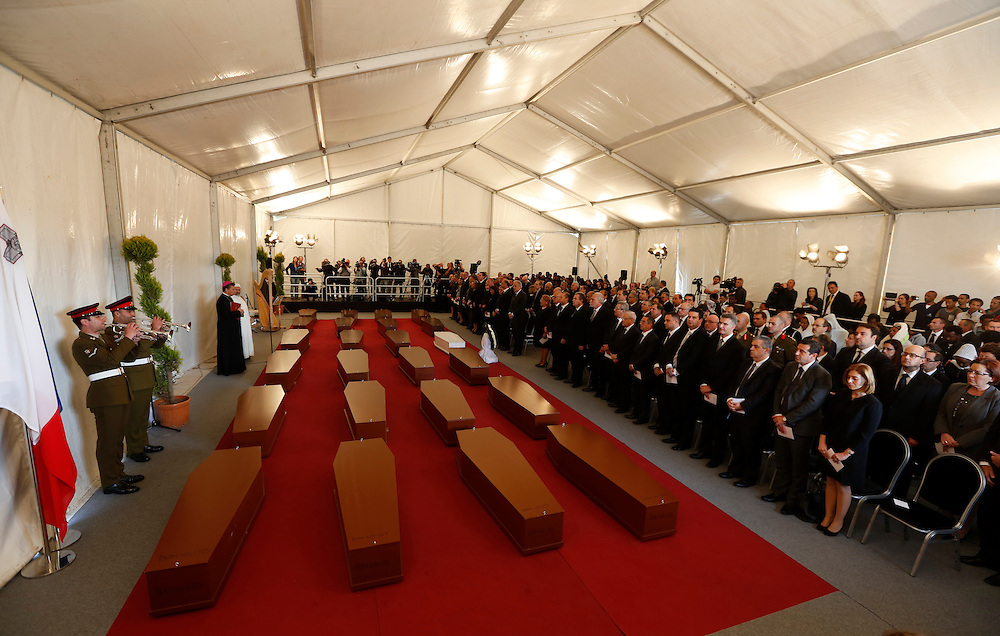 Armed Forces of Malta buglers play in front of the coffins with the bodies of 24 migrants during an inter-faith burial service at Mater Dei Hospital in Tal-Qroqq outside Valletta, April 23, 2015. European Union leaders who decided last year to halt the rescue of migrants trying to cross the Mediterranean will reverse their decision on Thursday at a summit hastily convened after nearly 2,000 people died at sea.  Public outrage over the deaths peaked this week after up to 900 migrants died last Sunday when their boat sank on its way to Europe from Libya.<br /> REUTERS/Darrin Zammit Lupi MALTA OUT. NO COMMERCIAL OR EDITORIAL SALES IN MALTA
