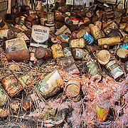 Hundreds of old leaking oil cans are strewn around the interior of the oil can van in the Old Car City junkyard in Georgia.