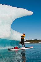 Man paddles stand up paddle board (SUP) looking up at iceberg on Bear Lake in Kenai Fjords National Park, Alaska.
