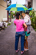 22 OCTOBER 2012 - HAT YAI, THAILAND:      A woman picks up a baby while her friend holds an umbrella for them during a rainy season shower in Hat Yai, Thailand. Hat Yai is the largest in southern Thailand. It is an important commercial center and tourist destination. It is especially popular with Malaysian, Singaporean and Chinese tourists.     PHOTO BY JACK KURTZ