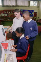 Multiracial group of secondary school pupils using computer in classroom,