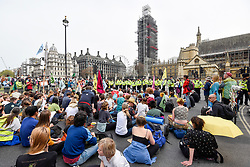 "© Licensed to London News Pictures. 23/04/2019. LONDON, UK.  Activists face police in at Parliament Square during ""London: International Rebellion"", on day nine of a protest organised by Extinction Rebellion.  Protesters are demanding that governments take action against climate change.  Police have issued a section 14 order for Parliament Square and expect that the occupation of the square will have concluded by the end of the day.  Photo credit: Stephen Chung/LNP"