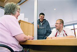 Two young men; one a wheelchair user; signing in at reception of day centre for homeless and vulnerably housed young people,