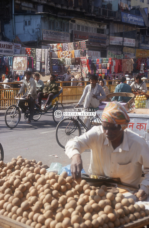 Chandni Chowk; a main shopping street in Delhi; India; with potato stall in the foreground; bicycle rickshaws and stalls,