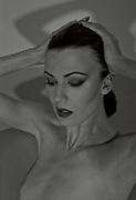 Black and White old Hollywood style image of a woman naked from the chest up.  Her hands lay upon her head as she gazes in front of her.