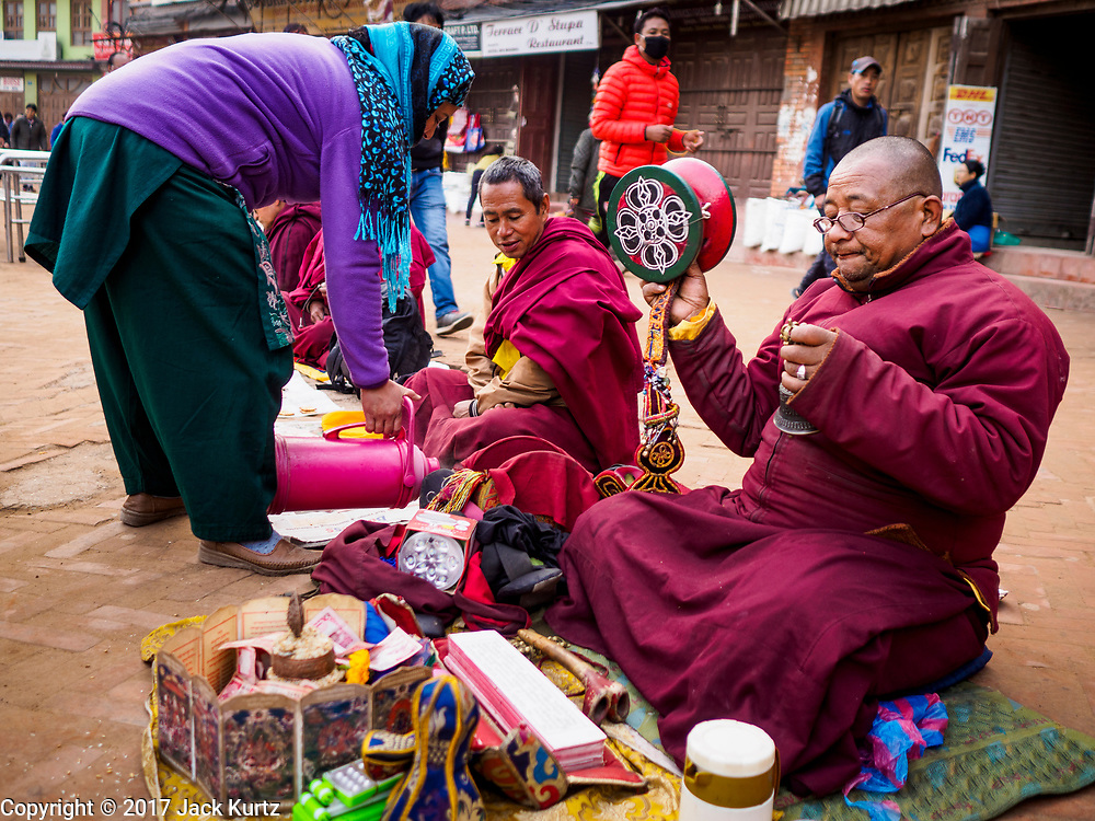 17 MARCH 2017 - KATHMANDU, NEPAL: A woman donates food and drinks to Buddhist monks during morning payers in front of Boudhanath Stupa in Kathmandu. The stupa is the holiest site in Nepali Buddhism. It is also the center of the Tibetan exile community in Kathmandu. The Stupa was badly damaged in the 2015 earthquake but was one of the first buildings renovated.         PHOTO BY JACK KURTZ