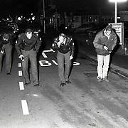 NLD/Zeist/19921031 - Zoekactie politie op het wegdek naar hulzen en kogels na schietpartij op de Slotlaan in Zeist