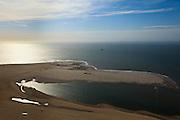 Nederland, Zuid-Holland, Gemeente Westland, 23-05-2011; Zandmotor, aanleg van kunstmatig schiereiland door het opspuiten van zand voor de kust ter hoogte van Ter Heijde. De sleephopperzuiger is verbonden met de persleiding die naar het schiereiland loopt. Aan de horizon een tweede sleephopperzuiger die zaan aan het innemen is..Wind, golven en stroming zullen het zand langs de kust verspreiden waardoor breder stranden en duinen ontstaan. De zandmotor is een experiment in het kader van kustonderhoud en kustverdediging. In de achtergrond de kassen van het Westland..Sand Engine, construction of artificial peninsula by the raising of sand for the coast of Ter Heijde (near the Hague). A trailing suction hopper dredger is connected to the discharge pipe that runs to the peninsula. On the horizon a second dredger is loading sand. .Wind, waves and currents will distribute the sand along the coast yielding wider beaches and dunes along the coastline. The Sand Engine is a experiment for coastal maintenance of coastal defense. In the background the Westland greenhouses..luchtfoto (toeslag); aerial photo (additional fee required).foto Siebe Swart / photo Siebe Swart