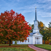 New England fall foliage at the white steeple Martha-Mary Chapel at the Wayside Inn Historic District in Sudbury, Massachusetts.<br />