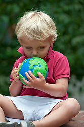 young boy holding and kissing a model of planet Earth