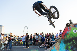 London, UK. 20th April 2019. A BMX rider uses the wooden ramp set up by climate change campaigners from Extinction Rebellion on Waterloo bridge as part of International Rebellion activities which have now lasted six days. Police officers today made a concerted attempt to try to clear the bridge of activists.