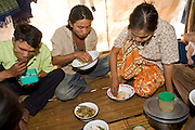 """25 FEBRUARY 2008 -- MAE SOT, TAK, THAILAND: Burmese migrant workers eat their lunches during their break on a commercial rose growing farm near Mae Sot, Thailand. There are millions of Burmese migrant workers and refugees living in Thailand. Many live in refugee camps along the Thai-Burma (Myanmar) border, but most live in Thailand as illegal immigrants. They don't have papers and can not live, work or travel in Thailand but they do so """"under the radar"""" by either avoiding Thai officials or paying bribes to stay in the country. Most have fled political persecution in Burma but many are simply in search of a better life and greater economic opportunity.  Photo by Jack Kurtz"""