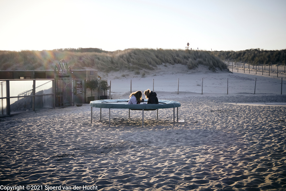 Twee vrouwen zitten op een trampoline aan het Zuiderstrand.   Two women are sitting on a trampoline on the Zuiderstrand.
