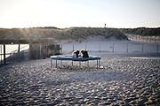 Twee vrouwen zitten op een trampoline aan het Zuiderstrand. | Two women are sitting on a trampoline on the Zuiderstrand.