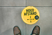 Nederland, Nijmegen, 30-4-2020 In een winkel, supermarkt, zijn stickers op de grond geplakt om de bezoekers te dwingen afstand van 1,5 ,anderhalve, meter te houden . Sticker, symbool,pictogram, associatie . Foto: Flip Franssen