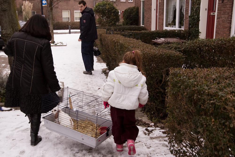 Een vrouw draagt met haar dochter de kooi van een konijn dat net bij de dierenarts vandaan komt