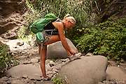 Fit blonde woman tying shoelace during the decent of the famous and difficut hiking trail down the Masca Barranco Gorge in Teneriffe. This trail leads from the high mountain village of Masca down to the Atlantic Ocean at Masca Beach.