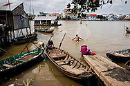 A young man fishes in the Mekong River in Can Tho with a fishing net. Robert Dodge, a Washington DC photographer and writer, has been working on his Vietnam 40 Years Later project since 2005. The project has taken him throughout Vietnam, including Hanoi, Ho Chi Minh City (Saigon), Nha Trang, Mue Nie, Phan Thiet, the Mekong, Sapa, Ninh Binh and the Perfume Pagoda. His images capture scenes and people from women in conical hats planting rice along the Red River in the north to men and women working in the floating markets on the Mekong River and its tributaries. Robert's project also captures the traditions of ancient Asia in the rural markets, Buddhist Monasteries and the celebrations around Tet, the Lunar New Year. Also to be found are images of the emerging modern Vietnam, such as young people eating and drinking and embracing the fashions and music of the West. His book. Vietnam 40 Years Later, was published March 2014 by Damiani Editore of Italy.