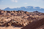 Mount Ellen, at the northern end of the Henry Mountains, rises prominently to the south of Goblin Valley State Park, in the San Rafael Swell, Utah. Admire fanciful hoodoos, mushroom shapes, and rock pinnacles in Goblin Valley State Park, in Emery County between the towns of Green River and Hanksville, in central Utah, USA. The Goblin rocks eroded from Entrada Sandstone, which is comprised of alternating layers of sandstone (cross-bedded by former tides), siltstone, and shale debris which were eroded from former highlands and redeposited in beds on a former tidal flat.