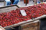 A street market stall selling red strawberries strawberry called Frutillas, lying in big mounds heaps.. Montevideo, Uruguay, South America