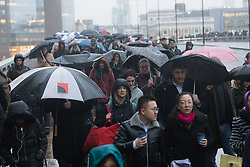 """© Licensed to London News Pictures. 15/01/2018. London, UK. Commuters cross London Bridge on their way to work during wet and windy weather this morning. Today is known as """"Blue Monday"""", the gloomiest and most depressing day of the year.. Photo credit: Vickie Flores/LNP"""