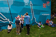Families linger in Hyde Park after another successful gold medal win, this time by Team GB triathlete Alistair Brownlee in the men's Triathlon during the London 2012 Olympic Games. The mid-week event surprisingly drew huge crowds into the capital's largest public (royal) park for an event, not usually attracting families with children who all enjoyed the fine weather and easy temperatures. A London 2012 merchandise shop was set up on the southern side and parents and kids used the exterior hoarding featuring iconic London landmarks such as Nelson's Column, St Paul's Cathedral and Tower Bridge, to relax against after an early start from homes around the country.