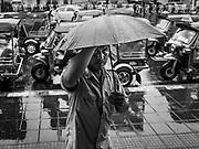 30 MAY 2017 - BANGKOK, THAILAND: A tuk-tuk (three wheeled taxi) driver takes shelter under an umbrella during a rain storm at Hua Lamphong train station.        PHOTO BY JACK KURTZ