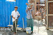 Woman labourers carrying concrete on a building site in Mandalay on 25th May 2016 in Myanmar