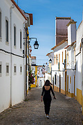 Stylish young woman walking in typical street scene of white and yellow houses, lanterns and narrow cobble street in Evora, Portugal